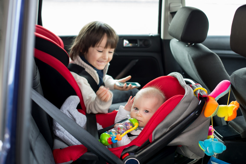 Child and baby in car
